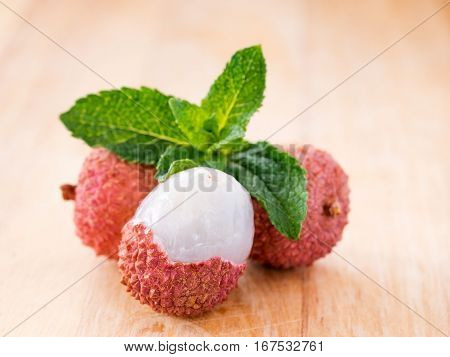 lichee fruit and mint leaf on wooden background close up