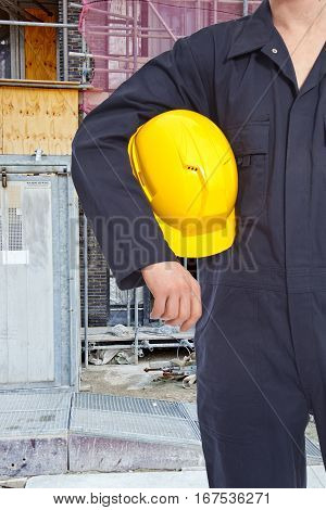 Construction worker with building and yellow helmet