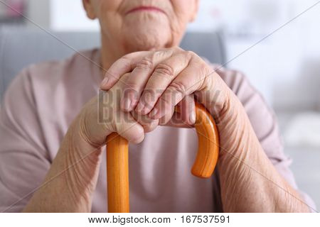 Elderly woman with walking stick at home, closeup