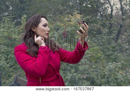 Woman in a red coat looking in the mirror. People