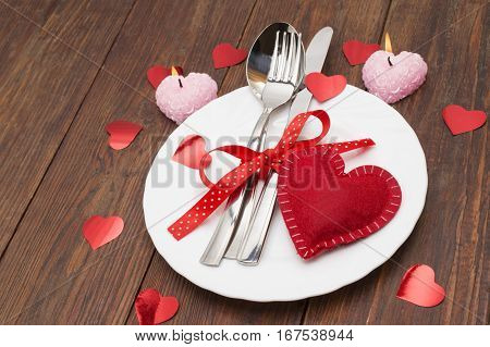 Table set for celebration Valentine's Day. Wooden table place setting with red heart for Valentine day.