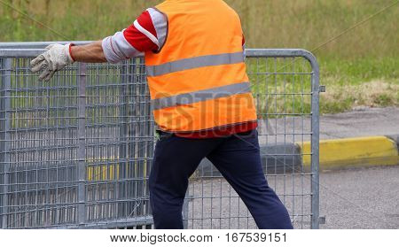 Worker With Orange High-visibility Vest While Moving The Fences