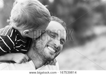 Child playing with his father. Child kissing father. Daddy playing active games with his son outside. Happy family portrait. Laughing dad with little boy enjoying together. Black and white photo.