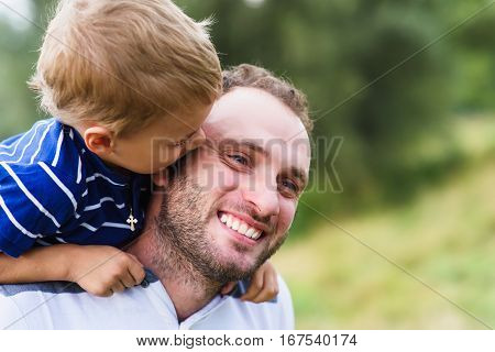 Child playing with his father. Daddy playing active games with his son outside. Happy family portrait. Laughing dad with little boy enjoying nature together.