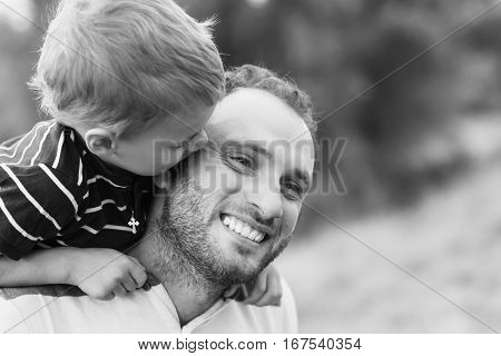 Child playing with his father. Daddy playing active games with his son outside. Happy family portrait. Laughing dad with little boy enjoying nature together. Black and white photo.