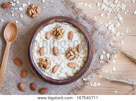 Organic oatmeal porridge in wooden bowl with nuts, honey, walnuts and raisins. Healthy breakfast - health and diet concept on the wooden table. Flat lay. Top view.