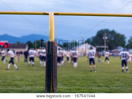 Yellow american football goal posts at school field with the student athletes on the field