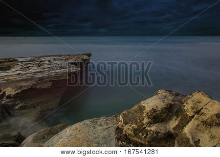 A long exposure of a land and seascape creates a gauzy stillness in a swirling sea around solid Pacific coastal rocks.