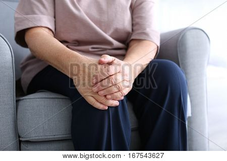 Elderly woman suffering from pain in knee at home, closeup