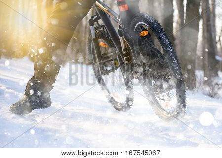 Professional Cyclist Riding the Bike on the Snowy Trail Lit by the Sun. Winter Extreme Sports Concept.