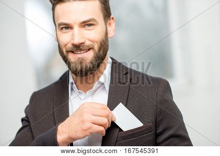 Elegant man in the suit putting business card into the pocket. White card to copy paste