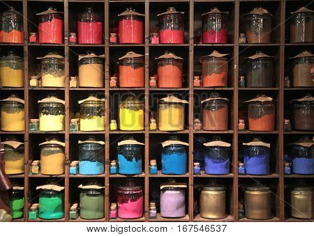 Various colorful dye in glass container on shelves in a paint shop for sale