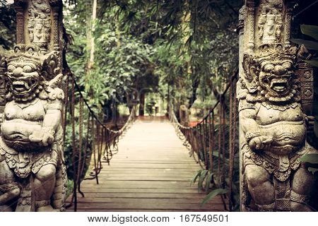 Old wooden hanging bridge leading to tropical forest with terrible statues of Asian Buddhism demons on both sides in vintage style