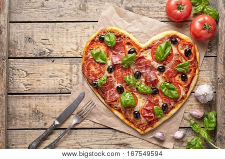 Pizza heart love Valentine's Day romantic dinner food with knife and fork. Prosciutto, olives, tomatoes, parsley, basil and mozzarella cheese meal served on vintage wooden table