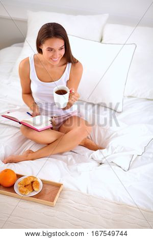 Young beautiful woman sitting in bed and writing in a copybook.