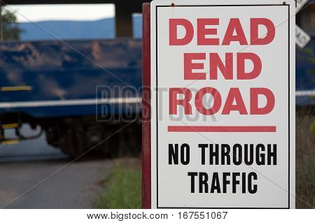 Dead End sign by railroad crossing with Diesel locomotive engine on steep trip into mountains of West Virginia