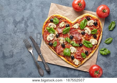 Heart shaped pizza love concept Valentine's Day flat lay romantic symbol dinner Italian food. Olives, prosciutto, champignons, tomatoes and mozzarella meal on blue table background.