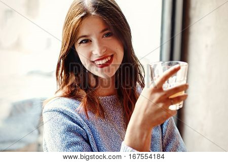 Happy Stylish Woman Holding Glass Of Drink And Smiling In Cafe On Background Of Light Window