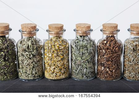 Assortment is aligned on a black table. Thyme, lemon balm, chamomile, sage, dandelion roots, wormwood with a white background.