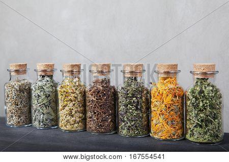 Assortment is aligned on a black table. Thyme, chamomile, sage, dandelion roots, calendula, hawthorn hemp