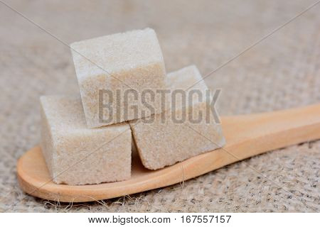 Wooden spoon with sugar cubes on table