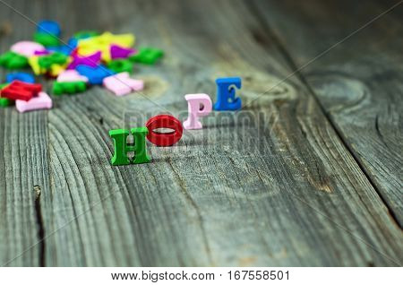 Words of hope from small wooden letters on a gray surface selective focus