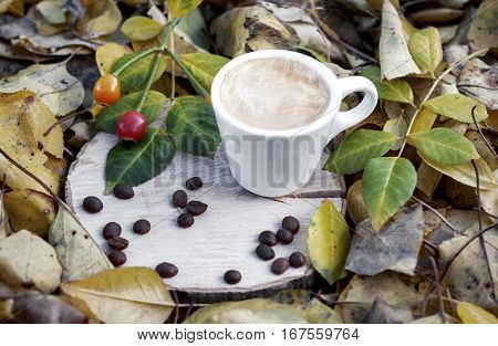 cup of espresso on a wooden stump among fallen autumn leaves vintage toning