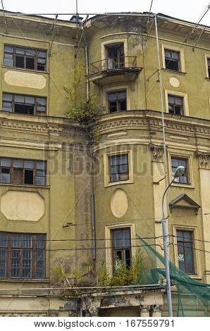 Part of the facade of the old house prepared for demolition. Cloudy day in October. Moscow.