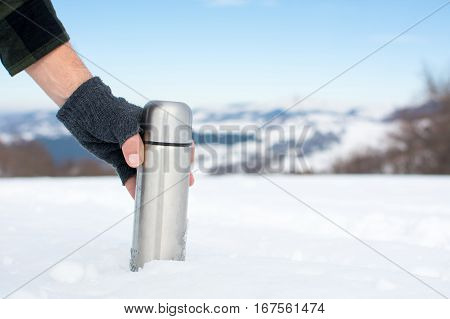 Man Holding Thermos In On A Snowy Mountain