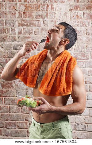Fit man holding a bowl of fresh salad on old red bricks background.