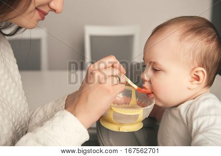 Mom feeding her baby girl with a spoon. Mother giving food to her eight-month child at home. Baby food. Close-up portrait.