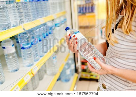 Woman choosing bottled mineral water in supermarket store