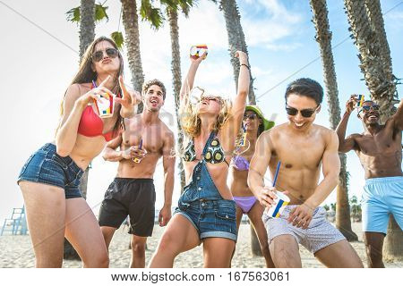 Group of friends having party on the beach dancing and drinking cocktails