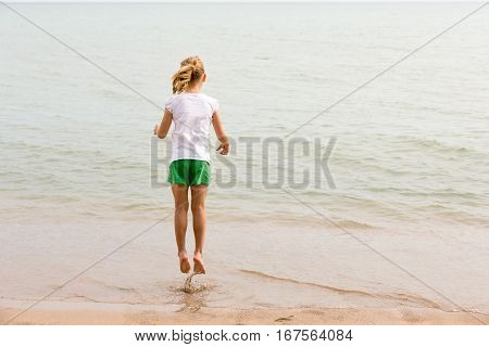 Girl jumping over water at a lakeshore. Viewed from behind with copy space if needed. Concepts could include childhood play joy vacation or many others.