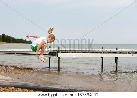 Girl jumping over water at a lakeshore. Copy space in sky if needed. Concepts could include childhood play joy vacation or many others.