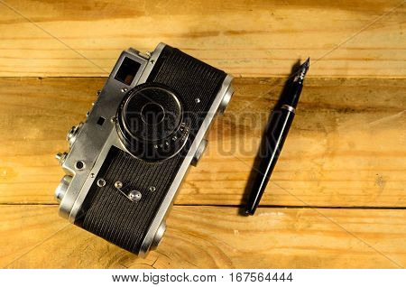 Old vintage soviet rangefinder camera and fountain pen on a wooden table