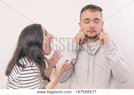 Woman Yelling At Her Boyfriend In Hysterics. Young Man Covers His Ears, Not Wanting To Listen To It