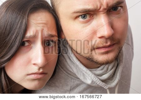 Young Couple With Dubious Looks Forward, Wrinkling His Face In Disbelief.