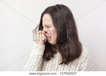 Girl with long hair plugs her nose because of disgusting smell