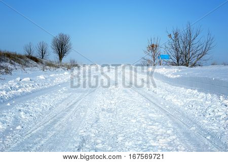 Country side empty road covered with snow on sunny day
