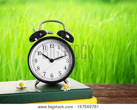 Alarm clock with books and flowers on wooden table against grass background. Time change concept