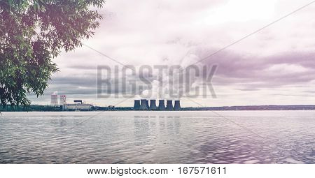 Environment protection concept. Nuclear power plant on the water tank. Smoke belching from the chimneys. Toned picture