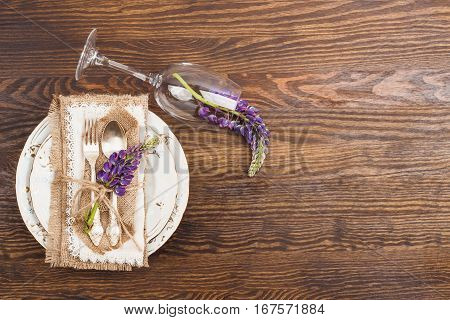 Tableware and silverware with puffy violet lupins on the wooden background