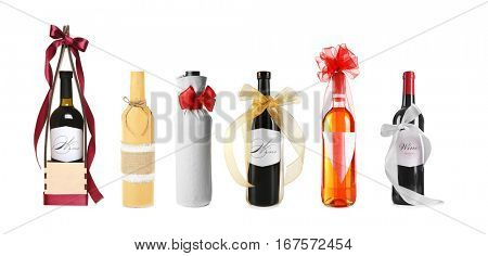 Set of wine bottles with festive decor on white background