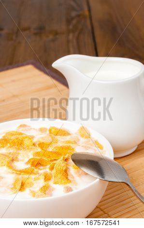 Healthy vegetarian breakfast, corn flakes, milk jug and spoon on napkin on rustic dark wooden table