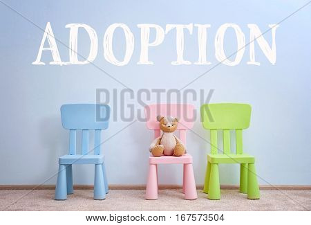 Adoption concept. Children chairs with toy on wall background