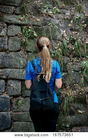 Girl with a rucksack in front of the moss wall.
