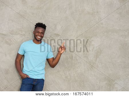 Confident Young Man Pointing And Smiling