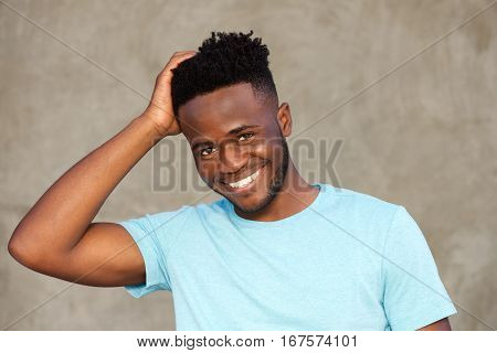 Handsome African Man Smiling And Standing With Hand In Hair