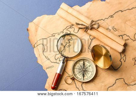 Compass, scroll, magnifier and old map on blue background. Columbus Day concept